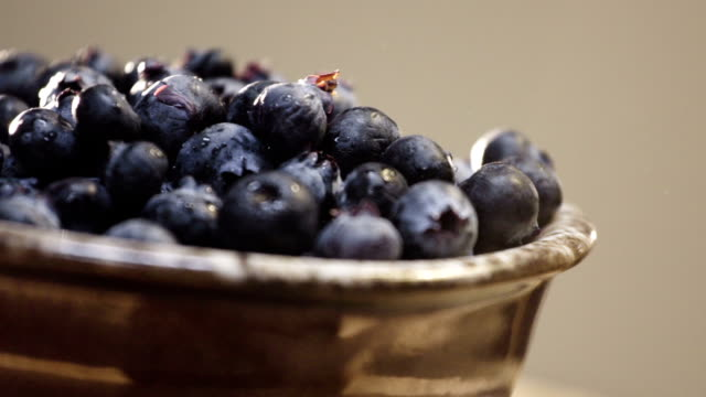 Closeup shot of fresh blueberries in a brown bowl video