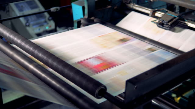 Close-up shot of fresh newspapers rolling on printing equipment. printed newspapers ready for folding printmaking technique stock videos & royalty-free footage