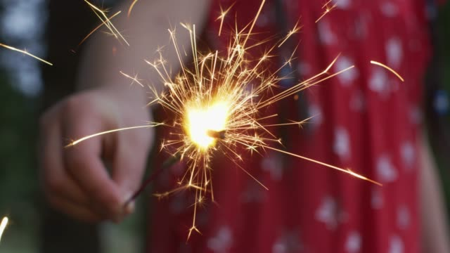 closeup shot of girl holding sparkler fireworks at 4th of july celebration. - giorno dell'indipendenza video stock e b–roll
