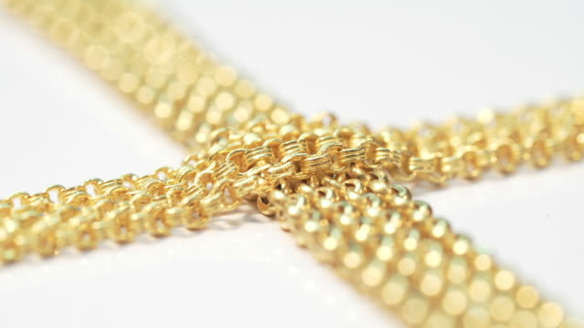 Closeup shot of gold necklaces with rotating