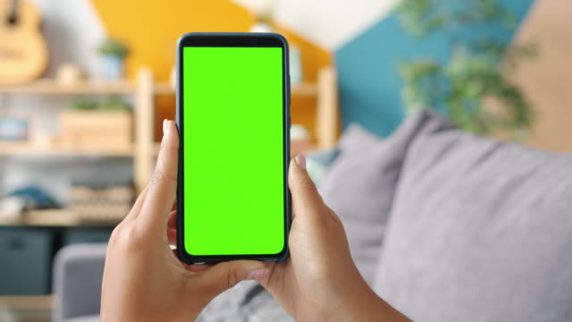 Close-up shot of green screen template smartphone in female hands at home video