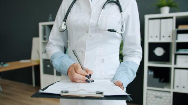 colpo ravvicinato di mano del medico che scrive nelle cartelle cliniche del paziente che lavora in ospedale - arto umano video stock e b–roll