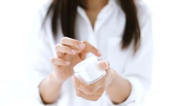 Closeup shot of hands applying moisturizer. Beauty woman holding a glass jar of skin cream. Shallow depth of field with focus on moisturizer video