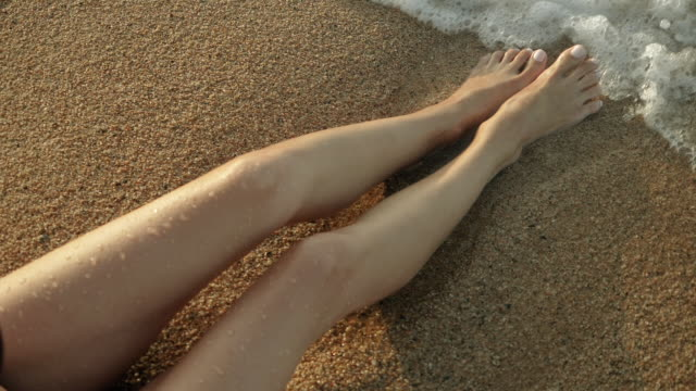 close-up shot of legs of beautiful young woman sitting on the beach on a sunny day. sea waves washing over tanned female feet. spain. slow motion. hd - загар стоковые видео и кадры b-roll