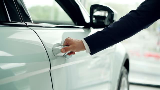 vidéos et rushes de gros plan de main mâle, ouverture de porte de voiture chez concessionnaire auto avec grande fenêtre à l'arrière-plan. vente de voitures, voitures luxueuses et notion de vendeur. - tentation