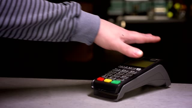 Close-up shot of man attaches hand with microchip implant to terminal making successful contactless payment. Close-up shot of man attaches hand with microchip implant to terminal making successful contactless payment implant stock videos & royalty-free footage