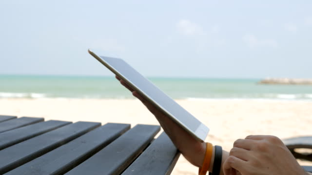 Close-up shot of man hands typing on tablet computer on the beach video