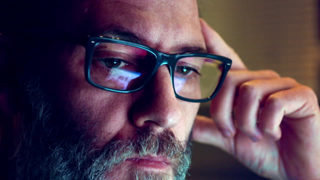 Close-up shot of man wearing glasses browsing the internet