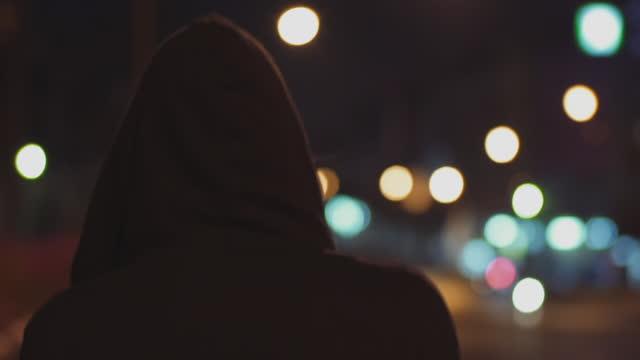 vídeos de stock e filmes b-roll de closeup shot of man with back against camera with black hood in a deserted neighborhood - capuz