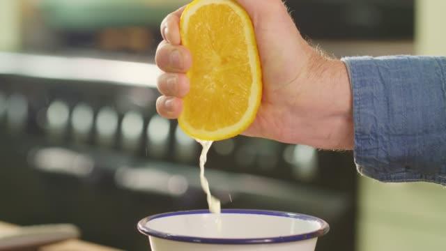 Closeup Shot Of Man's Hand Squeezing Orange Juice Into Bowl