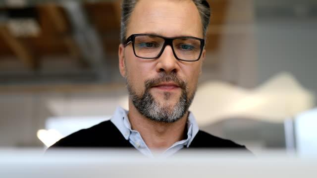 Close-up shot of mature businessman using laptop