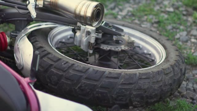 Close-up shot of motorcycle wheel on ground after an accident crash or fall . Slow motion