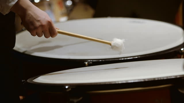 Close-up shot of musician playing kettledrum in concert video