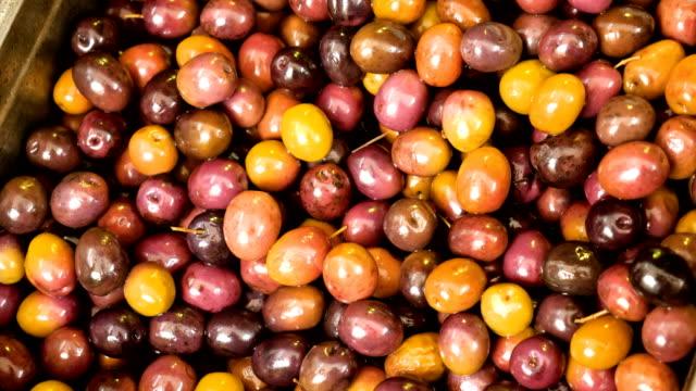 stockvideo's en b-roll-footage met close-up shot van gepekelde olijven uit een vat op de voedselmarkt. 4k - olijf