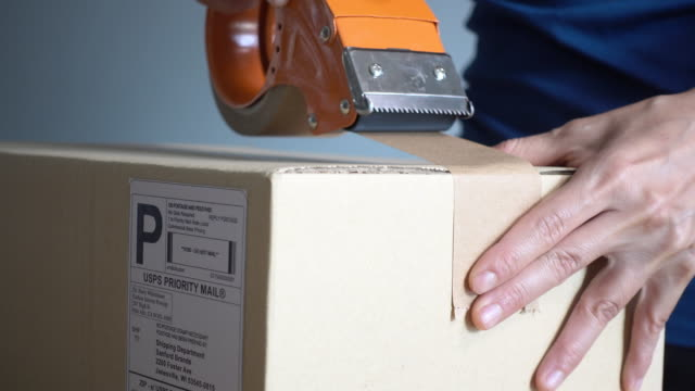 Close-up Shot of Professional Warehouse Worker Packing Cardboard Box Ready for Shipment Close-up Shot of Professional Warehouse Worker Packing Cardboard Box Ready for Shipment post office stock videos & royalty-free footage
