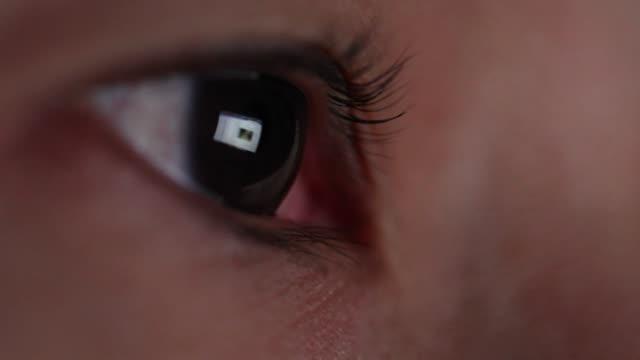 närbild skott av reflektioner av laptop skärm i kvinnor öga. - missbruk koncept bildbanksvideor och videomaterial från bakom kulisserna