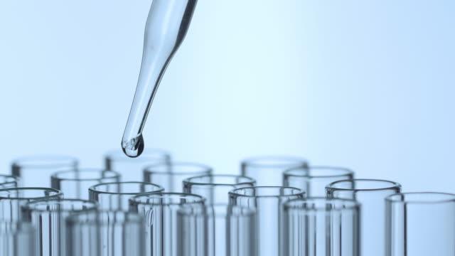 vídeos de stock, filmes e b-roll de close up disparado do líquido do gotejamento do cientista no tubo de teste - tubo objeto manufaturado