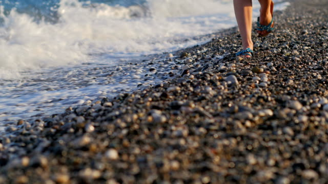 close-up shot of slim woman's legs walking on a pebble coast at sunset video