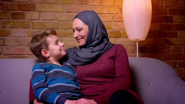 close-up shot of small boy and his muslim mother in hijab smiling into camera incline head to each other at home. - традиционная одежда стоковые видео и кадры b-roll