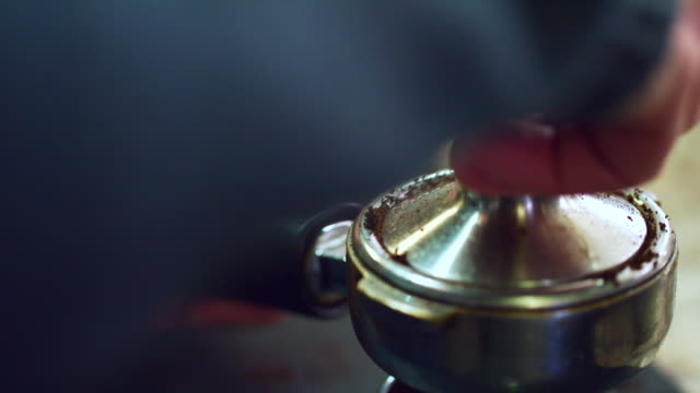 close-up shot of someone tamping (pressing) coffee grounds in a portafilter (espresso machine) - grindare video stock e b–roll