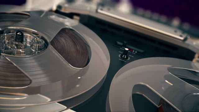 closeup shot of spinning reels on old analogue reel-to-reel audio tape recorder - cassetta video stock e b–roll