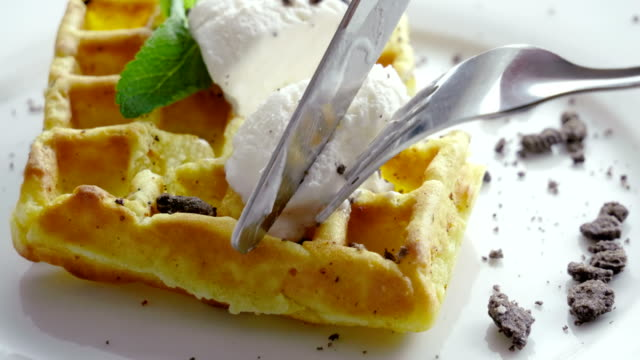 Close-up shot of sweet waffles with ice cream and mint on a white plate. 4K Eating Breakfast. Close-up shot of women's hands cutting viennese waffles with a knife and fork. 4K fork stock videos & royalty-free footage