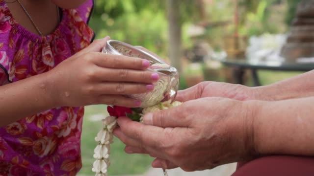 vídeos de stock, filmes e b-roll de foto de close-up da tailandesa pequena criança menina despejando água para idosos mais velho mão em slow motion (120 fps). conceito de festival tailandês songkran - ano novo budista