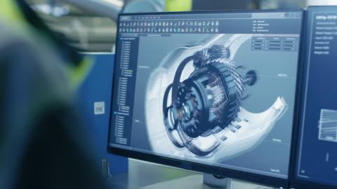 vidéos et rushes de gros plan photo du modèle cao 3d du moteur indiqué sur écran d'ordinateur. dans le fond de fabrication d'usine avec le travail de personnes. - lourd