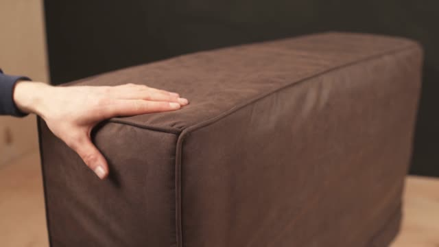 Close-up shot of the man's hands tightening leather cloth on the couch. Sofa made at the furniture factory, carpentry master touches the soft upholstery