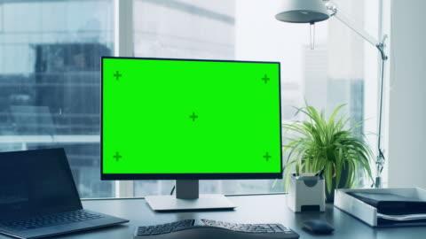 vídeos y material grabado en eventos de stock de toma de primer plano del escritorio de oficina con verde maqueta pantalla ordenador personal permanente en él. elegantes habitaciones con vistas al gran distrito de negocios de la ciudad. - escritorio