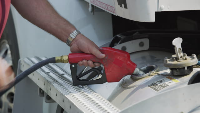 Closeup shot of truck driver filling up fuel tank. Closeup shot of truck driver filling up fuel tank.  Fully released for commercial use. refueling stock videos & royalty-free footage