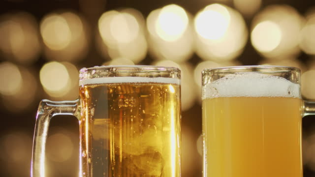 Close-up shot of two friends clang beer spilling beer bokeh background. Close-up shot of two friends clang beer spilling beer bokeh background household fixture stock videos & royalty-free footage
