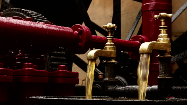 Closeup shot of two industrial faucets pouring oil on an hydraulic engine video