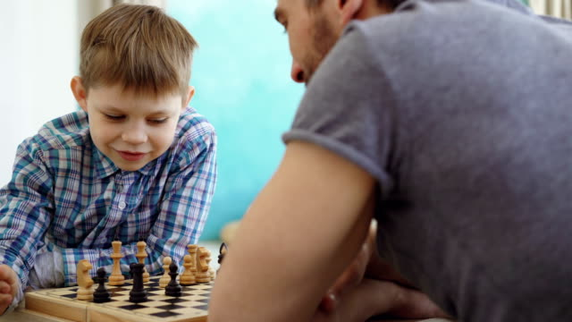 Close-up shot of two people father and son playing chess, thinking about next move and moving chessmen on board. Intellectual hobby and happy family concept. Close-up shot of two people father and young son playing chess, thinking about next move and moving chessmen on board. Intellectual hobby and happy family concept. plank timber stock videos & royalty-free footage