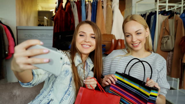 Close-up shot of two young women making selfie with smart phone after shopping in clothing store. First they are posing and laughing, then watching photos on screen