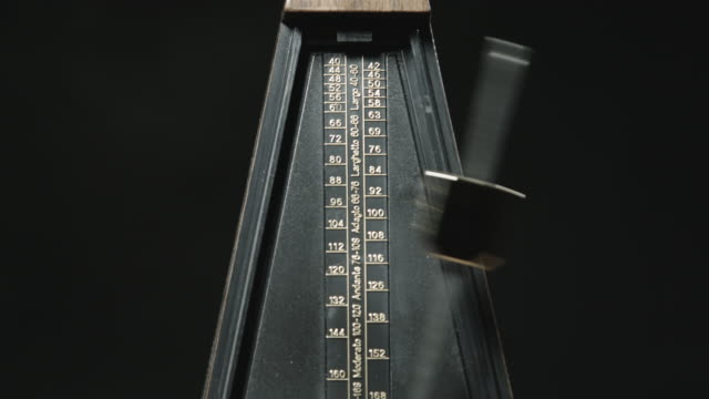 Close-up shot of vintage metronome with golden pendulum