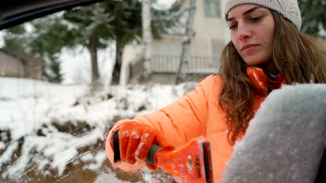 Closeup shot of woman cleaning car wipers from snow video