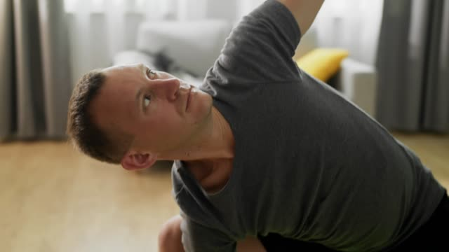 Close-up shot of young man doing yoga in the morning in his living room video