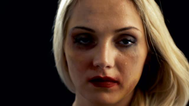 Primer plano tiro llorando triste había herido a mujer rubia mirando hacia abajo y luego en la cámara. Tema de la violencia. Fondo es negro aislado. - vídeo