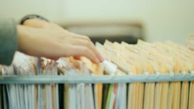 vídeos y material grabado en eventos de stock de primer disparo: mujer abre un cajón, mira las notas. trabajar con los documentos archivados - suministros escolares
