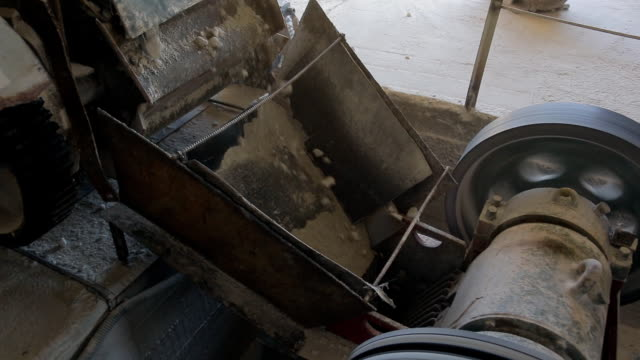 Close-up shows the mechanism by which poured gravel at the factory video