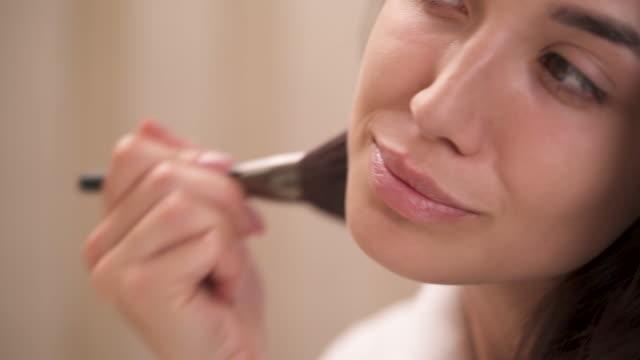 vidéos et rushes de une vue de côté gros plan d'une face de la jolie jeune femme aux cheveux bruns. application de poudre pour le visage avec un pinceau sur sa joue gauche, le menton, le nez. - pinceau à maquillage