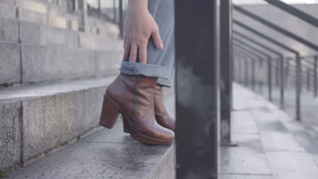 close-up side view of female caucasian legs stepping down the stairs and stopping because of ankle pain. woman in jeans and brown boots suffering from fast pace of life. healthcare, lifestyle. - fare un passo video stock e b–roll
