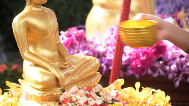 vídeos de stock, filmes e b-roll de vista lateral de close-up: dar os pêsames a uma estátua de buda, deitando água nele - ano novo budista