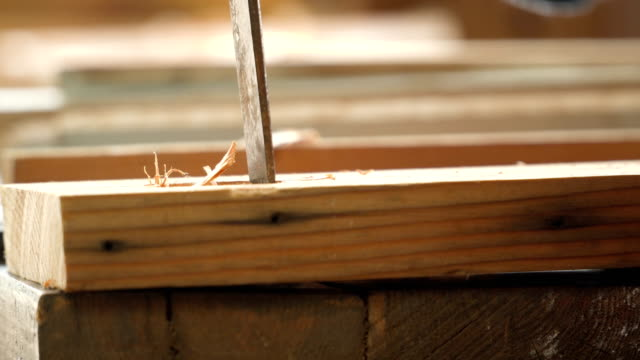 close-up side view: senior carpenter's hand carving on wood in the workshop house