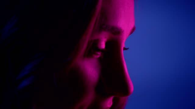 stockvideo's en b-roll-footage met close-up zijaanzicht schieten van jonge mooie vrouwelijke gezicht glimlachend gelukkig in de voorkant van de camera met neon blauwe achtergrond - portrait background