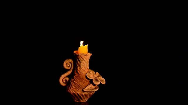 close-up single candle flame isolated on black background - candeliere video stock e b–roll