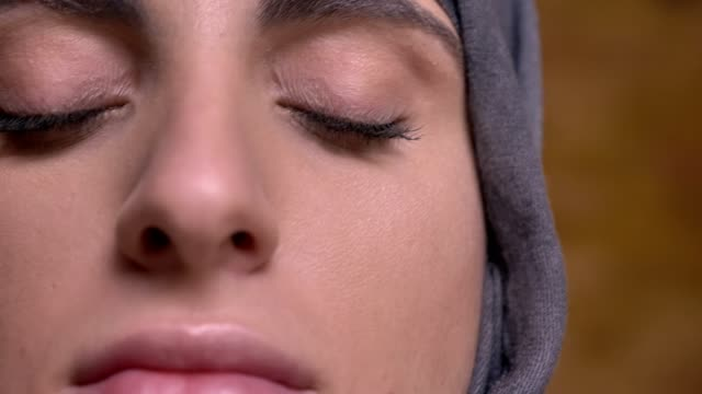 närbild slide shot av kvinnliga händer gör make-up med hjälp av platt borste för muslimsk kvinna i hijab på bricken vägg bakgrund. - hijab bildbanksvideor och videomaterial från bakom kulisserna