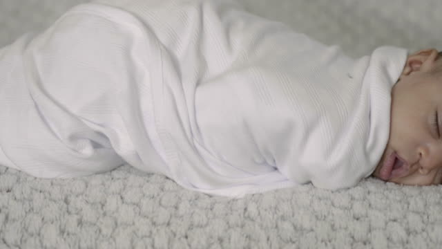 Close-Up Sliding Shot of A Baby Wrapped in a Blanket While Napping video