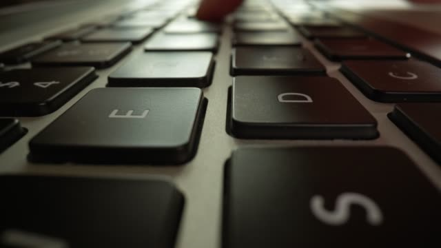 крупным планом раздвижные выстрел пальцев набрав клавиатуру ноутбука. супер макро выстрел. женщина, работающая на своем ноутбуке дома. выс� - близко к стоковые видео и кадры b-roll